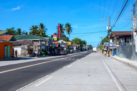 Dumaguete, the Philippines - 07 Apr 2020: empty highway of philippine village during coronavirus quarantine. Modern filipino lifestyle. Stores and stall closed during pandemic community quarantine. Редакционное
