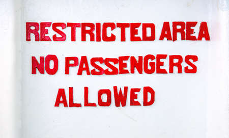 Red sign Restricted area No passenger allowed on white background. Prohibition for passengers of ship, vessel or boat. Rustic letters painted on white wall. Stencil typography prohibition sign