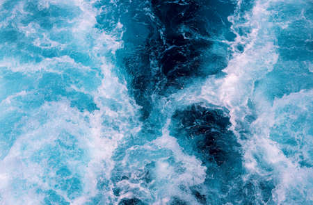 Natural sea foam after motor boat. Seascape perspective view. Maritime transportation on cruise ship or motor boat. White wave on oceanic surface. Deep blue water of open sea . Nautical background Фото со стока