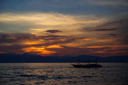 Sunset sea landscape with native boat. Philippines travel photo of beautiful seaside. Early morning seascape sun and cloud. Blue orange scenic sky view. Tropical seaside on sunrise. Summer vacation