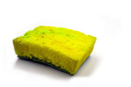 Used yellow sponge for dishwashing photo on white background. Foam rubber sponge with microbe and bacteria. House cleaning tools. Used household item. Everyday Non-biodegradable garbage. Age concept