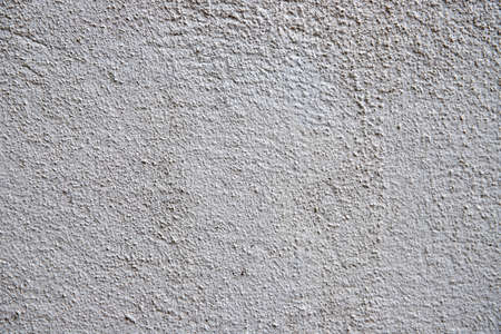 White plaster painted wall with grit and noise. Cracked wall closeup photo. Architecture detail background. Empty concrete wall. Grungy surface of painted cement. Abstract grainy texture