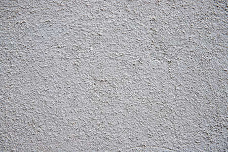 White plaster painted wall with grain and noise. Cracked wall closeup photo. Architecture detail background. Empty concrete wall. Grungy surface of painted cement. Abstract grainy texture