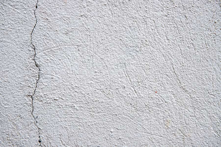 White plaster painted wall with grain and cracks. Cracked wall closeup photo. Architecture detail background. Empty concrete wall. Grungy surface of painted cement. Abstract grainy texture