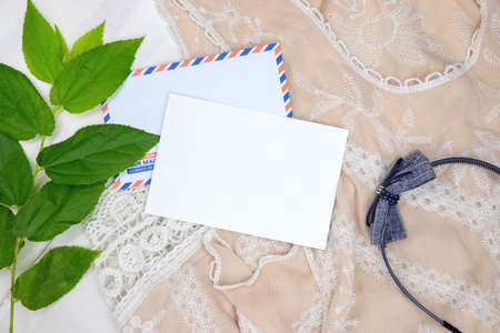Black card with air mail envelope. Bohemian background with lace dress, headband and sunglasses. Summer vacation top view composition. White paper postcard mockup. Summer travel card with holiday wear