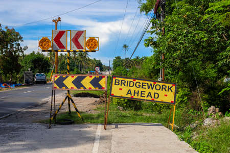 Bridgework ahead yellow sign on road construction site. South Asia economical development concept. Road construction in the Philippines. Warning sign on rad. Tropical country travel or road trip Фото со стока