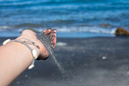 Woman hand and black sand on beach day. Sand in hand relaxing photo. Beach day leisure. Volcanic beach with black sand. Female hand with sand on seaside background. Travel ban country lockdown concept