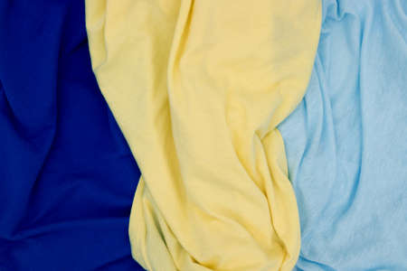 Blue yellow fabric top view. Bright colored textile photo texture. Folded fabric with wrinkles for pattern mockup. Blank textile surface. Fashion or retail industry banner template