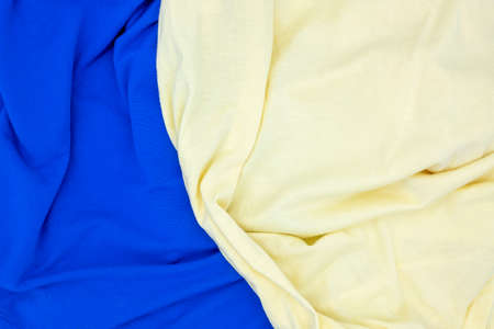 Blue yellow fabric top view. Colored textile photo texture. Folded fabric with wrinkles for pattern mockup. Blank textile surface. Fashion or retail industry banner template