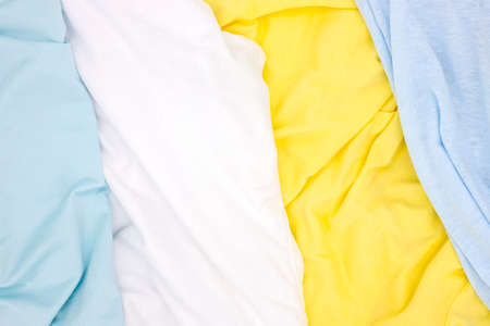 Pastel colored fabric top view. Yellow blue white textile photo texture. Folded fabric with wrinkles for pattern mockup. Blank textile surface. Fashion or retail industry banner template