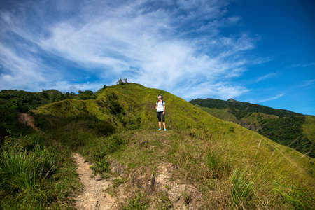 Tropical island landscape with female tourist and mountains. Natural parkland hills and forest Summer travel adventure outdoors. Hiking woman alone on mountain. 스톡 콘텐츠