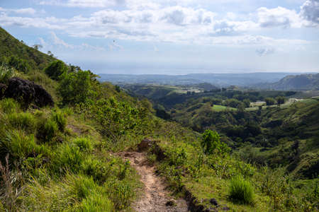 Tropical island landscape with green hills and hiking path. Green summer nature scenic view. South Asia traveling. Hiking tour in the Philippines. Untouched environment of tropical island
