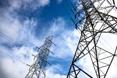 Electric tower and wires on blue sky. Telecommunication and internet provider equipment. Communication tower with wire line. Electrical pylon view from ground. Transmission tower skyscape