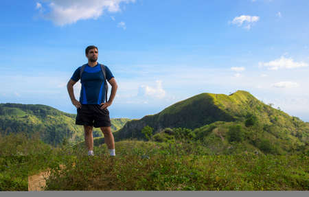 Man trekker on mountain landscape background. Summer countryside hiking trail view with male tourist. Man in treking or hiking outfit. Active lifestyle. Sport fit look in nature. Outdoor adventure 스톡 콘텐츠