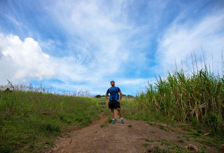 Trekker on trail on natural landscape background. Summer countryside hiking trail view with male tourist. Man in treking or hiking outfit. Active lifestyle. Sport fit look in nature
