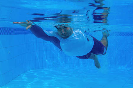 Man swimming in blue water. Sportsman training in blue swimming pool. Swimming pool underwater photography. Young man in swimwear. Fitness and active lifestyle training 스톡 콘텐츠