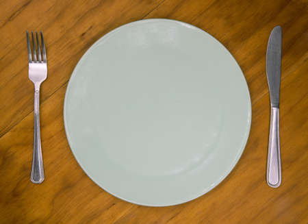 Empty plate with knife and fork on wooden background. Cutlery and plate on wooden backdrop. Photo of an empty plate for the restaurant menu. The concept of waiting for food.
