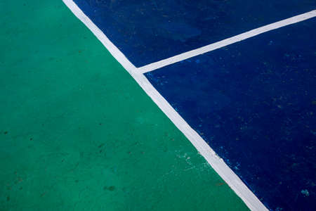 Sport field with color blocks and white line marks, perspective view photo. Tennis court cover in green and blue colors. Business competition concept. Sport game playground with markup