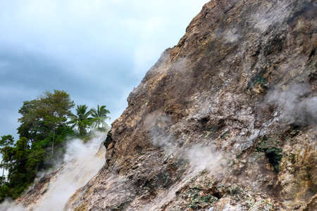 Smoking mountain rocks above green trees, volcanic island nature. Abstract mountain landscape with geyser smoke. Volcano caldera view. Canyon hiking banner template. Mountain and palm tree landscape