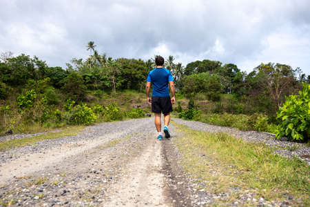 Young man walking on bumpy road in summer natural landscape. Summer outdoor hiking adventure. Empty village road and walking man. Sportsman on natural parkland of tropical island