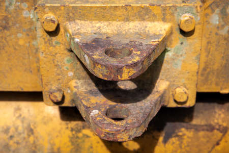 Old mechanism detail, yellow painted special equipment closeup photo. Truck or tractor trailer connector. Rustic metallic hitch on yellow vehicle. Construction equipment detail
