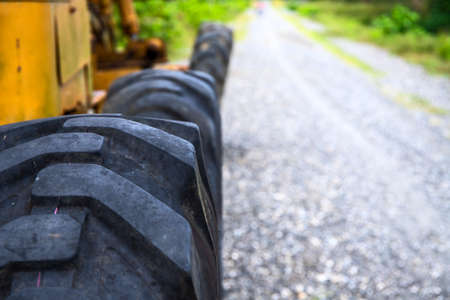Rustic black tire of tractor and road perspective view. Heavy machinery detail in outdoor landscape. Road construction site concept with copy space. Bumpy road and grader. Summer industrial landscape