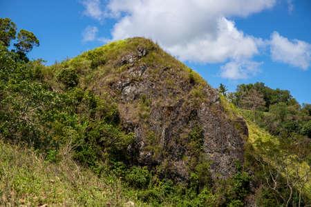 Green mountain rock peak under blue sky optimistic landscape. Rural land scenery. Summer travel hiking in green hills. Untouched nature parkland. Volcanic island relief