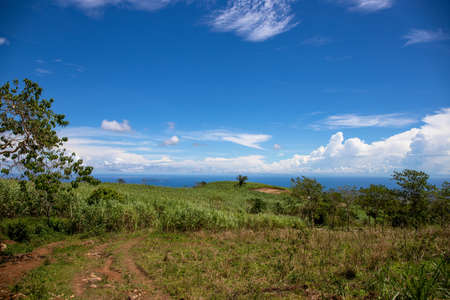 Green mountain and distant ocean under blue sky. Sunny rural landscape. Rural land scenery. Summer travel hiking in green hills. Untouched nature parkland. Volcanic island relief