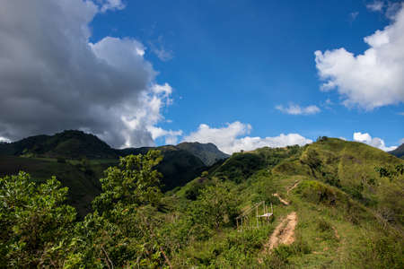 Green mountain range and walking path under blue sky landscape. Rural land scenery. Summer travel hiking in green hills. Untouched nature parkland. Volcanic island relief