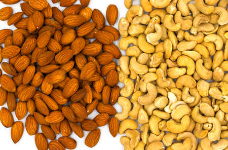 Cashew and almond pile on white background. Natural organic nut kernel. Protein superfood or healthy snack. Nuts pile scattered on white table top view. Granola package design. Healthy eating Banque d'images