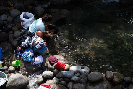 Dumaguete, the Philippines - 23 Jan 2021: woman washing clothes in river. Rustic village lifestyle in South Asia. Household duties on woman. Tough life conditions in asian village. Female daily shores