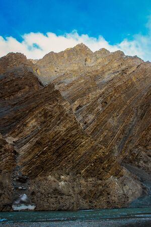 Geological Layers / Rocky textures of a weathered mountain face in Spiti Valley, Himachal Pradesh, India. Close up of a Brown & Yellow Rock Formation in the Himalayas. Scenic image of nature concept. Explore the environment. Discover the beauty of the earth.