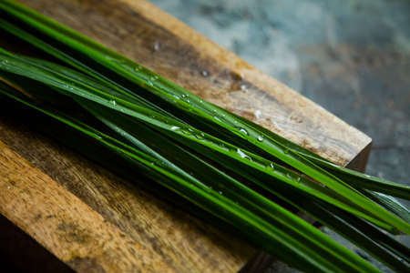 Fresh lemongrass or citronella grass on rustic wooden board. Herb used for healthy eating.