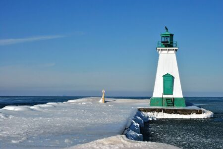 Lighthouse on an ice covered pier on lake ontario,canada 版權商用圖片