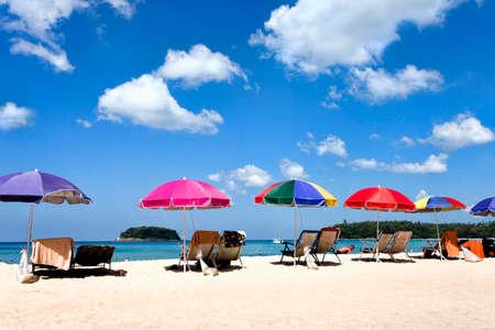 tourist attraction: Beach umbrellas and sunbeds on the beach, sunny