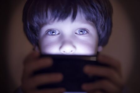 relation: Small child playing on a smartphone, boy Stock Photo