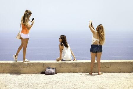 self dependent: Three girlfriends make a selfie on the sea beach, Europe