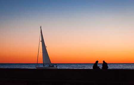 Silhouettes of people and yacht with a big sail on the sea as background, night