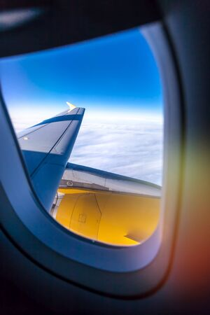 A skyscape through a full window of a plane, a part of a wing and a turbine Stock Photo