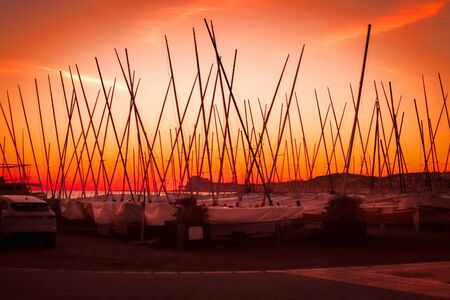A lot of yachts with tall masts at the pier at sunset, orange sky, dark, many masts
