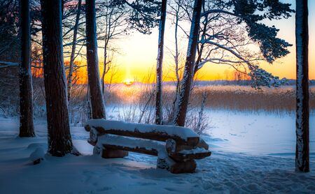 A wide snow space with a wooden bench at sunset, red sun, vast
