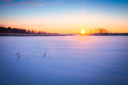 A wide snow space at sunset, red sun, space, empty, nobody