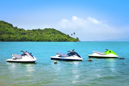 Three scooters on water, wide blue sky, colorful