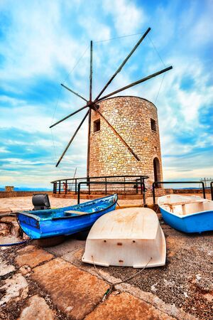Big windmill, cloudy sky, 3 old boats, colorful
