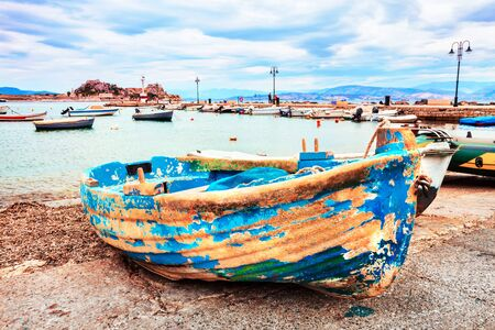The old fishing blue boat, the bay with boats, pier in Rhodes Banco de Imagens - 132124327