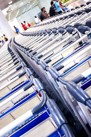 A tilted picture of rows of trolleys at the airport, many, passengers
