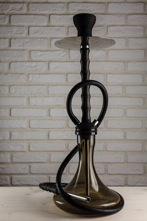 wooden hookah on a white wooden table on brick wall background