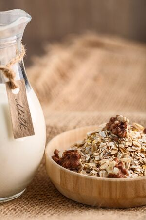 Dry rolled oatmeal with walnuts in wooden bowl on textile background. milk jug.