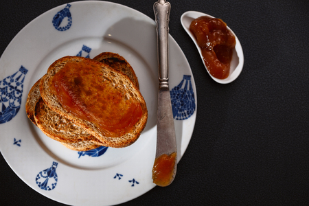 toasts with apple jam and knife on black background. Top view Stock Photo