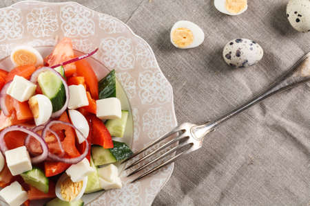 fresh vegetable salad with quail eggs and cheese in pink plate on the table